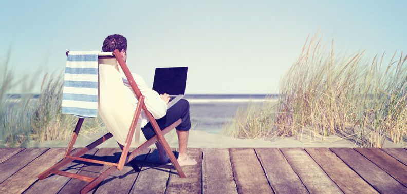 free businessman working on his laptop by the beach